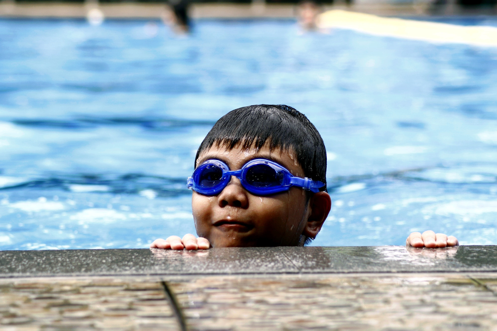 young boy with a pair of goggles in a swimming pool